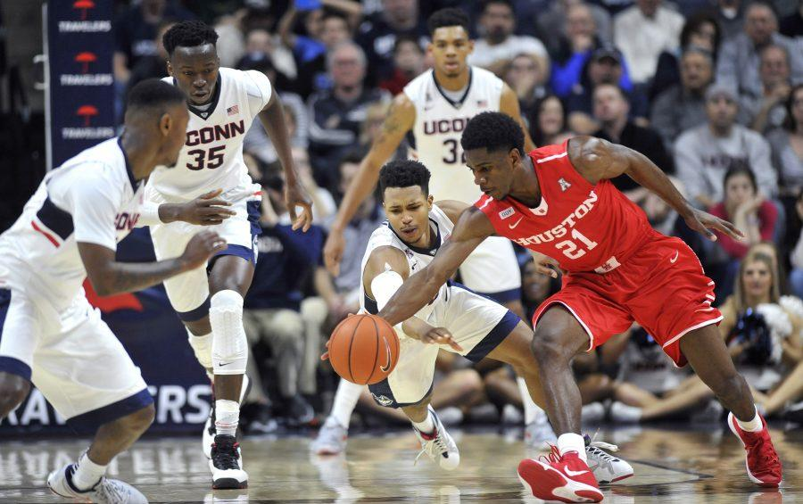 Connecticut's Jalen Adams (2) dives on the floor for a steal against Houston's Damyean Dotson (21) at Gampel Pavilion in Storrs, Conn., on Sunday, Feb. 28, 2016. Houston won, 75-68. (Photo by Tribune News Service)