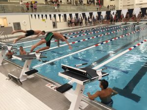 Two swimmers take their inaugural starts off the blocks in the new swimming pool. The pool is 40 meters long, so swimming and diving events can take place concurrently, unlike at the team's former pool at Wheeling.