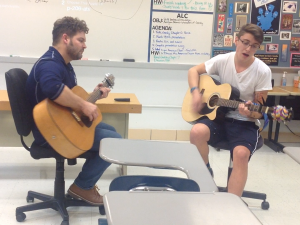 English teacher Michael Andrews helps junior Mike Gambino practice for Roundtable and Guitar Club's open mic night on Dec. 14.