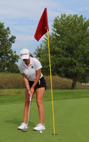 Kate Riesing secures a close putt on the green.